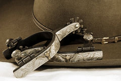Silver Spurs and a Cowboy Hat. Western themed close-up of fancy silver spurs and a cowboy hat on a white surface (sepia tint added royalty free stock photography