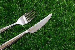 Silver stainless steel of fork and knife. On artificial grass Stock Photo