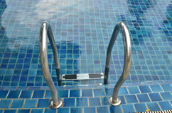 Silver stairs into a clear and fresh water pool Royalty Free Stock Photography