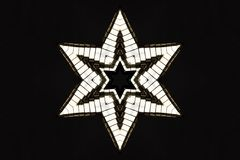 Silver Star. A shiny six pointed star on a black background Stock Photography