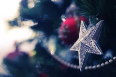 Christmas decorations. Silver star and garland on the Christmas tree Royalty Free Stock Image