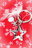 Silver star and white feather. On a red floral textile for a colourful Christmas background with pretty white corner vignetting Stock Image