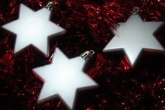 3 silver stars. Silver Christmas stars laying in red tinsel Royalty Free Stock Photography
