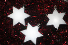 3 silver stars(2). Silver Christmas stars laying in red tinsel Stock Images
