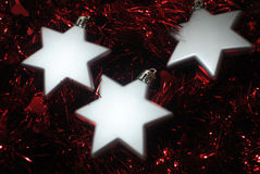 3 silver stars(3). Silver Christmas stars laying in red tinsel Royalty Free Stock Photography