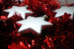 3 silver stars(4). Silver Christmas stars laying in red tinsel Royalty Free Stock Photo
