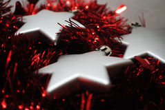3 silver stars(5). Silver Christmas stars laying in red tinsel Royalty Free Stock Image