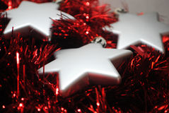 3 silver stars(6). Silver Christmas stars laying in red tinsel Royalty Free Stock Images