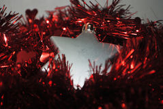 Silver stars. Silver Christmas star laying in red tinsel Stock Photo
