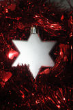 Silver stars (2). Silver Christmas star laying in red tinsel Stock Photos