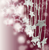 Silver Stars garland on pink blur background. Christmas and New Year Decorations. Stars garland on pink blur background Stock Photos