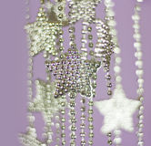 Silver Stars garland on purple background Stock Photo