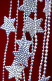 Silver Stars garland on red background Stock Photo
