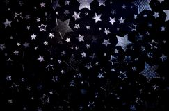 Silver stars scattered on a black background. Royalty Free Stock Image