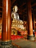 Silver statue of Buddha, devotion and worship in China. Columns, temple, religion, art and architecture, beauty and fascination in an historic site stock image