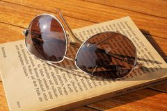 Silver Steel Framed Aviator Sunglasses on Top of Book during Daytime Royalty Free Stock Image
