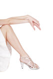 Silver stilettos. Long slim legs of woman in silver stilettos sitting on white background put her arms on knees Royalty Free Stock Image