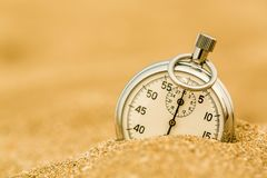 Silver Stopwatch in sand on beach Royalty Free Stock Images