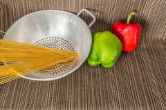 Silver strainer with spaghetti and peppers Royalty Free Stock Images