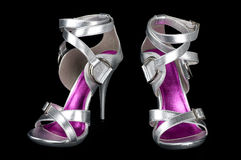 Silver strappy stiletto heels. Isolated on black background Stock Photos