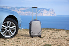 Silver suitcase near the car Royalty Free Stock Photography