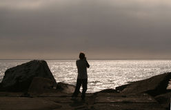 Silver Sunrise. Boy taking a picture of the afterglow of a sunrise Stock Image