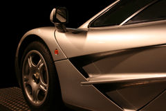 Silver supercar. Side of silver super car with a black background Stock Photography