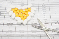 Silver surgical scissors with pile of pills as heart. Silver surgical scissors on bottom right of pile of white and yellow pills as heart for painkiller on Stock Photos