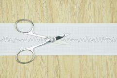 Silver surgical scissors put on paper of heart line wave Stock Images