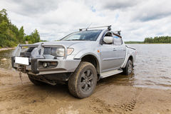 Silver SUV in the water on the background of the lake Stock Image
