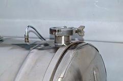 Silver Tank. Stainless Steel Gas Tank with lockable cap and steel strap and line connection Royalty Free Stock Images