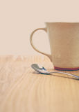Silver tea spoon and ceramic coffee cup Royalty Free Stock Photography