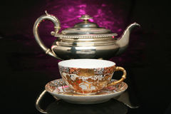 Silver teapot and an antique chinese cup of tea Stock Photo