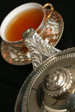 Silver teapot pouring tea Royalty Free Stock Image