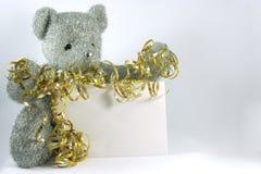 Silver Teddy Bear. A silver Teddy bear holding gold ribbon and a blank envelope stock photos
