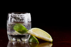 Silver tequila. Shot served on the rocks in a small glass with a lime wedge and salt on the rim Stock Photo