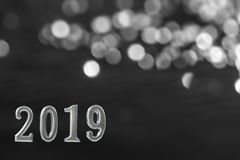 Silver text of 2019 over shinny candle, on black wall.New year concept. background, royalty free stock images