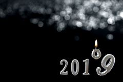 Silver text of 2019 over shinny candle, on black wall. with the nine number kicking the height end of the year concept royalty free stock images