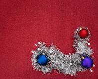 Silver tinsel garland and Christmas baubles on red glitter festi Royalty Free Stock Photos
