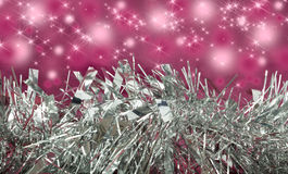 Silver tinsel/garland with pink sparkle background Royalty Free Stock Photos