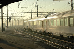 Silver Train In Early Morning Fog. Silver train leaving Brugges, Belgium station in early morning fog Royalty Free Stock Photos