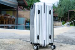 The silver travelling luggage is ready for summer beach and pool Stock Image