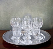 Silver tray with crystal glasses on a grunge background Royalty Free Stock Photo