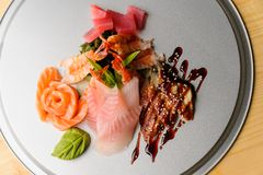 Silver tray with delicacy. Silver tray with such a delicacy as sashimi. Salmon in the form of flower, the leaf of wasabi, big shrimps, bunch onion, eels under royalty free stock photo