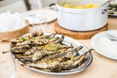 Silver tray full of delicious fish mackerel and pot of potatoes stock images