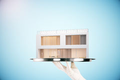 Silver tray with modern cottage. Hand holding silver tray with modern cottage, 3D Rendering Stock Photography