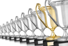 Silver trophies. Row of silver trophies and one gold isolated on white stock image