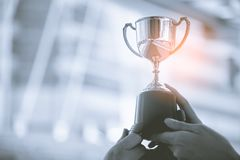 Silver trophy with city background. Success and achievement concept. Sport and cup award theme.  royalty free stock photography
