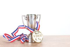 Silver trophy with gold medallion on a ribbon. Entwined through the handles conceptual of a win in a competition or championship with copy space stock photos