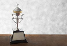 Silver trophy on wooden table on bokeh background. Winning awards with copy space. Silver trophy on wooden table on bokeh background. Winning awards with copy stock image